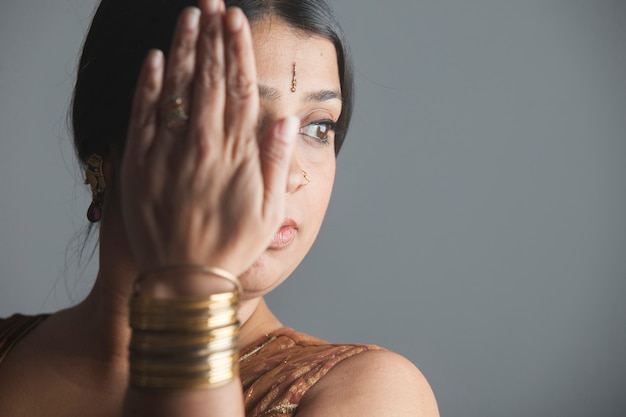 Портрет грустной индийской женщины, закрывающей лицо рукой