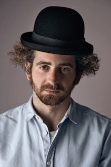 밝은 회색에 고립 된 t- 셔츠를 재미있는 검은 중산 모자와 가벼운 데님 버튼을 입고 곱슬 머리를 가진 슬픈 찾고 젊은 수염 된 유태인 남자의 초상화.