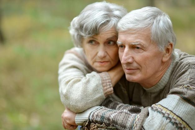秋の公園で悲しい年配のカップルの肖像画