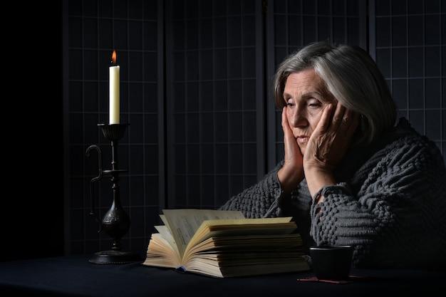 本と悲しい年配の女性の肖像画