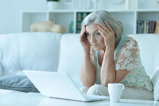 ノートパソコンで悲しい年配の女性の肖像画