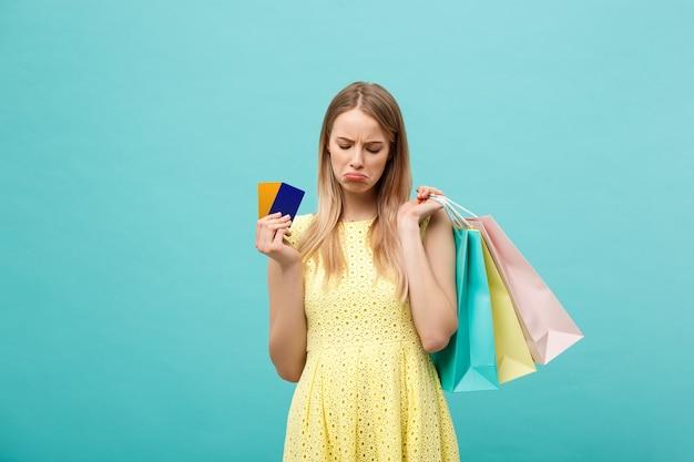 青い背景で隔離の買い物袋と銀行カードを保持している悲しい女性の肖像画