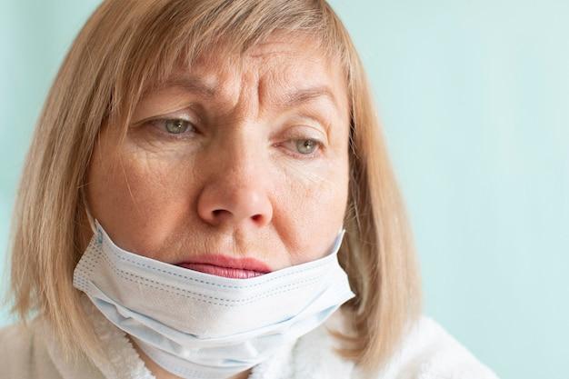 Портрет грустной женщины в медицинской маске из-за эпидемии коронавируса