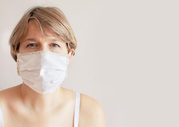コロナウイルスの流行のために医療用マスクを着用している悲しい女性の肖像画。