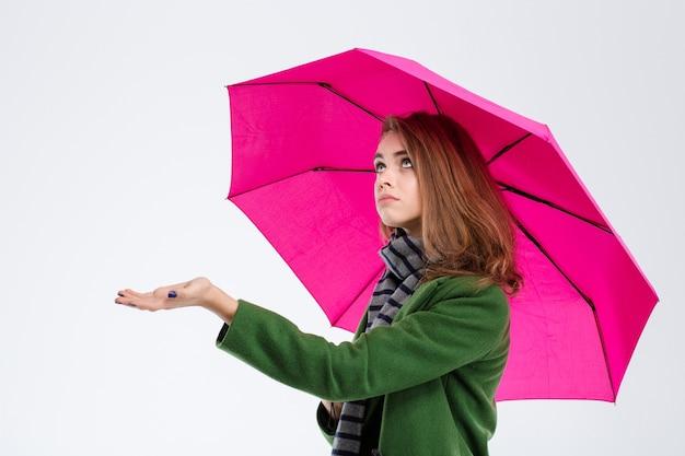 Портрет грустной женщины с зонтиком на белом фоне