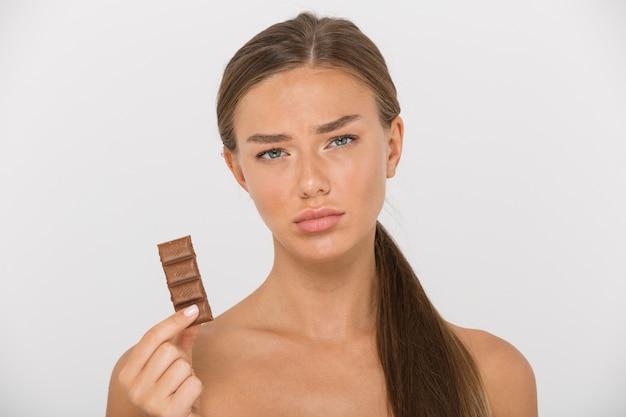孤立したチョコレートの断片を保持している悲しい若いトップレスの女性の肖像画