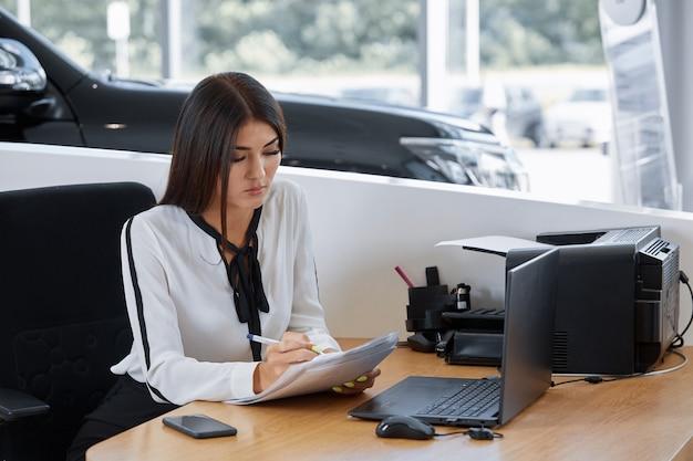 Портрет менеджера по продажам, сидящего за столом в автосалоне автосалона
