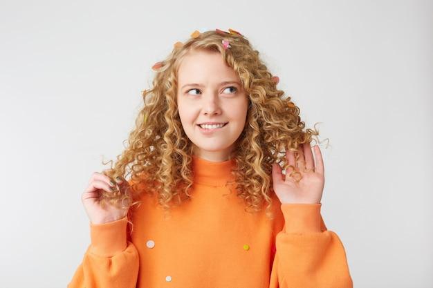 横を見て満足している女の子の肖像画は彼女の髪で遊んで、彼女の唇を噛み、彼氏とのデートについて考えています