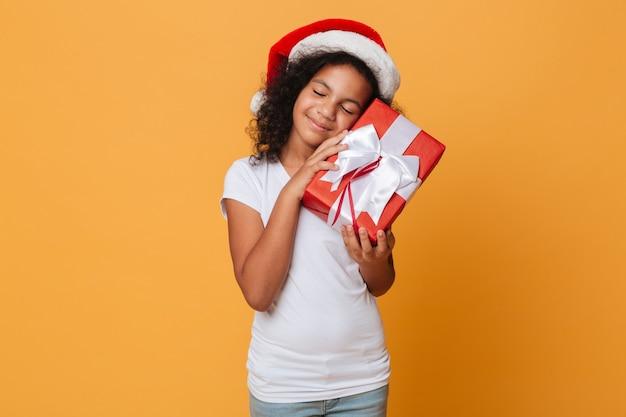 クリスマスの帽子に身を包んだ満足のいく小さなアフリカの女の子の肖像画