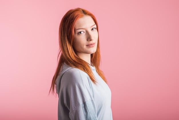 Портрет довольной рыжей девушки в студии на розовом фоне