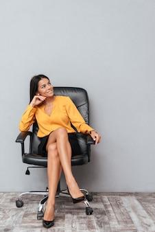 Портрет довольной улыбающейся деловой женщины, сидящей в кресле
