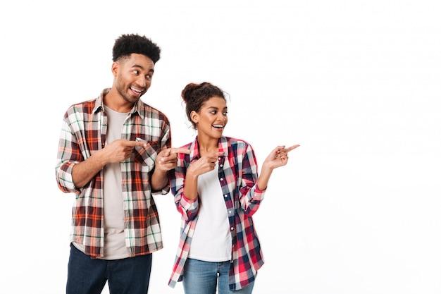 一緒に立っている満足している若いアフリカカップルの肖像画