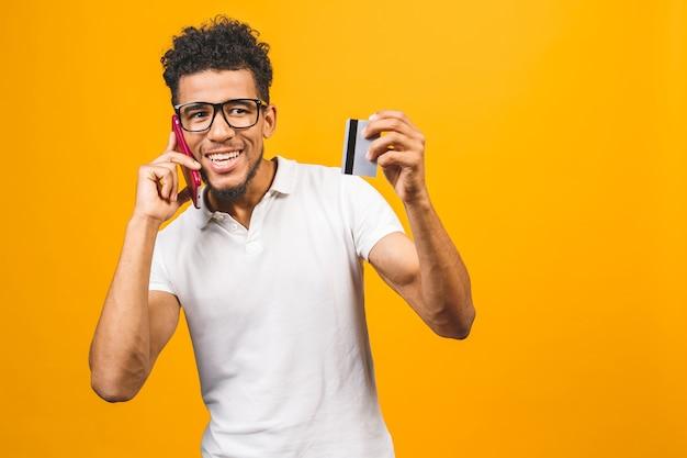 プラスチック製のクレジットカードを示すカジュアルな服を着て満足している若いアフリカ系アメリカ人男性の肖像画