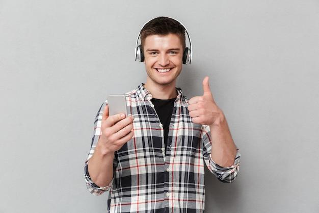 Портрет довольного молодого человека, слушающего музыку
