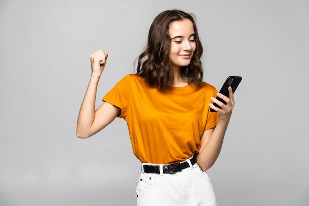 携帯電話を持って、灰色の上に孤立して祝う満足している若い女性の肖像画