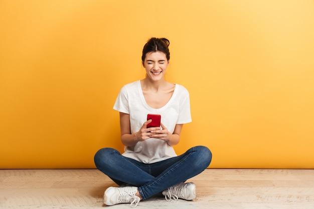 携帯電話を保持している満足している若い女性の肖像画