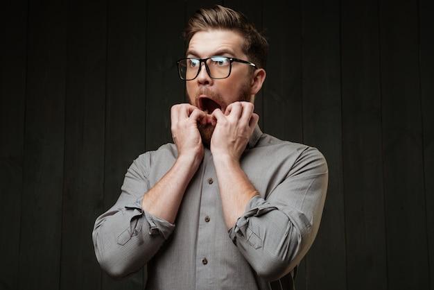 Портрет испуганного бородатого мужчины в очках, смотрящего в сторону, изолированного на черной деревянной поверхности
