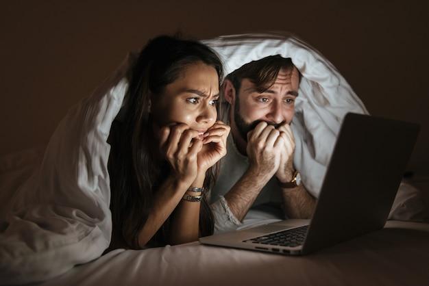 Портрет испуганной молодой пары, смотрящей фильм