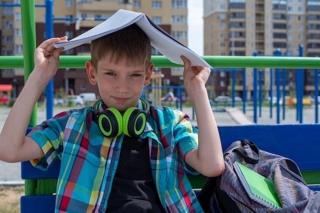Портрет школьника прячется от солнца за школьной тетрадью. мальчик не хочет ходить в школу. вернуться к школьной концепции