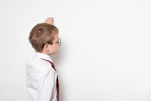 Портрет школьника в круглых очках. делает вид, что пишет на доске. белый фон.