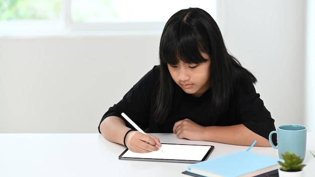 Портрет школьницы с помощью цифрового планшета, делать домашнее задание онлайн дома. концепция онлайн-образования.