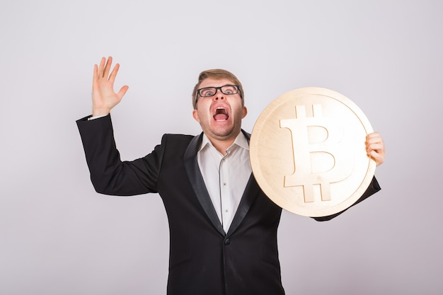 Портрет кричащего бизнесмена держит в руках большой золотой биткойн. человек в панике из-за краха криптовалюты.