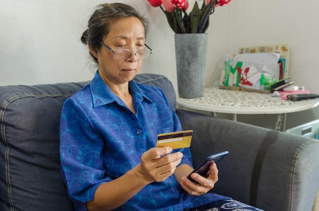 온라인 쇼핑 휴대 전화와 신용 카드를 들고 수석 아시아 여자의 초상화