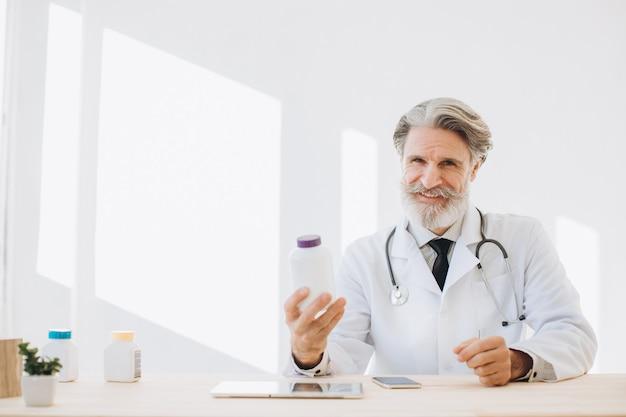 病院で薬のボトルを保持している先輩医師の肖像画