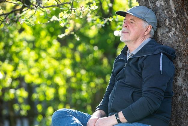 Портрет пожилого человека на открытом воздухе, сидящего на скамейке в парке, оптимизм, хорошее здоровье, выражение пенсии или концепция пенсии
