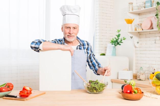 Портрет старшего человека, готовит зеленый салат, держа руку над белым плакатом на кухне
