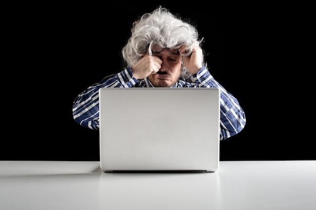 Портрет старшего мужчины, протирающего усталые глаза, сидя перед портативным компьютером на белом столе. черный фон
