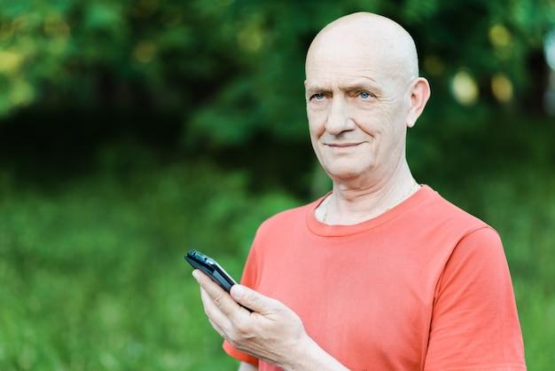 공원에서 그의 손에 전화로 서 수석 남자의 초상화. 고품질 사진