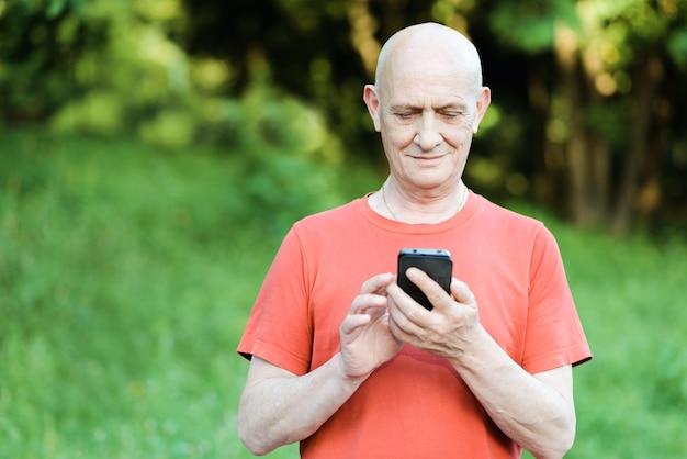 공원에서 그의 손에 전화로 서 수석 남자의 초상화.