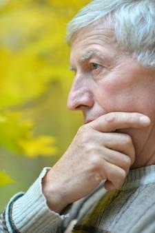 屋外で何かを考えている年配の男性の肖像画