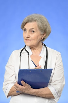 Портрет старшего врача женщины на синем фоне