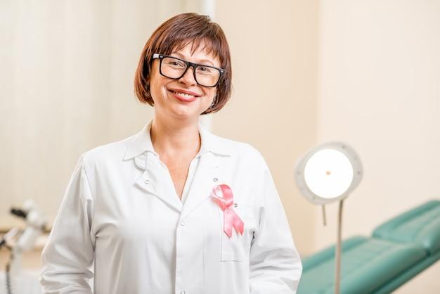 オフィスに立っている医療用ガウンに援助リボンと年配の女性婦人科医の肖像画