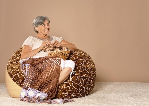 肘掛け椅子に座って編み物をする年配の女性の肖像画