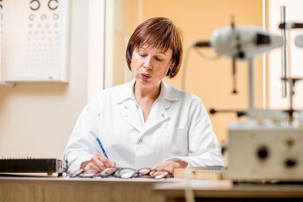 オフィスでの作業中にさまざまな光学デバイスと眼鏡を持って座っているユニからの年配の女性眼科医の肖像画