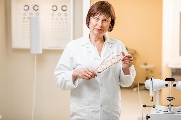 オフィスで視力検査のためのレンズを持って立っている年配の女性眼科医の肖像画