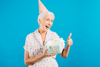 Portrait of a senior woman with birthday gift gesturing thumbs up on blue backdrop