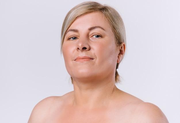 白い背景の上のカメラを見ている清潔で自然な肌を持つ年配の女性の肖像画。高品質の写真