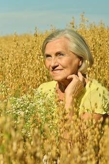 フィールドに花を持つ年配の女性の肖像画
