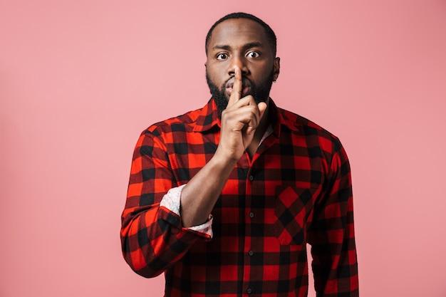 Портрет серьезного африканца в клетчатой рубашке, стоящего изолированно над розовой стеной и демонстрирующего жест молчания