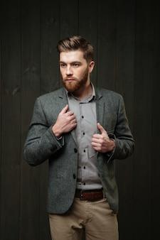 Портрет серьезного бородатого мужчины в повседневном костюме, стоящего и смотрящего в сторону, изолированного на черном деревянном фоне