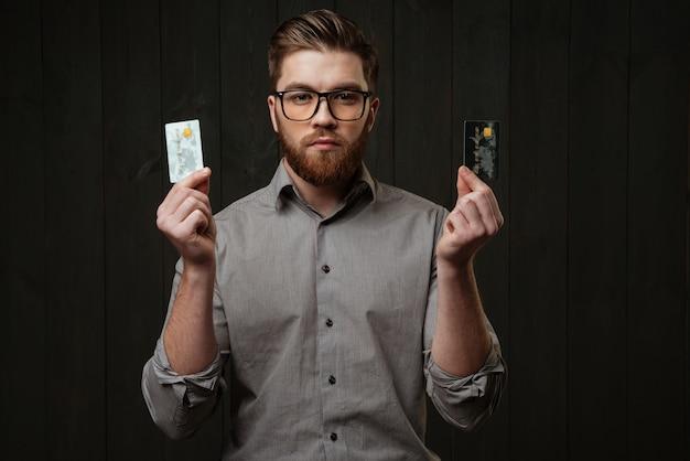 Портрет серьезного бородатого мужчины в очках, держащего кредитные карты и смотрящего вперед, изолированного на черной деревянной поверхности