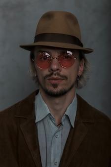 Портрет серьезного бородатого молодого человека в винтажных красных очках, в элегантной шляпе, в модном коричневом пиджаке и классической полосатой рубашке в студии у серой стены. брутальный парень.