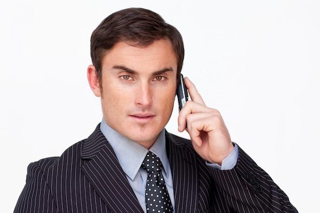 白い電話機での深刻なビジネスマンの肖像