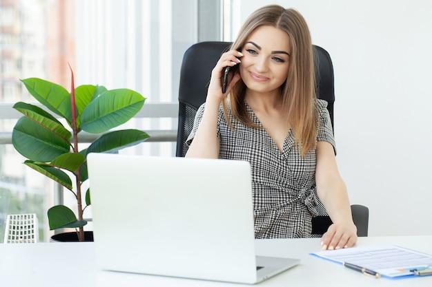 Портрет серьезной деловой женщины, использующей ноутбук в офисе.