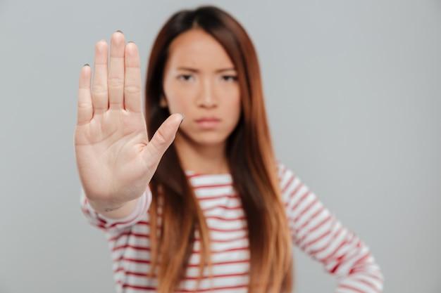 Портрет серьезной уверенной женщины, показывающей жест остановки