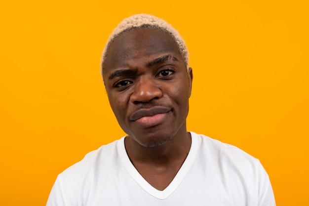 オレンジ色の深刻な不機嫌なハンサムな黒金髪アフリカ人のクローズアップの肖像画
